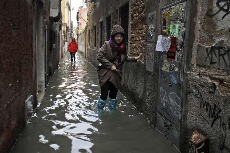 威尼斯近日淹大水,民眾努力涉水前進。(美聯社)