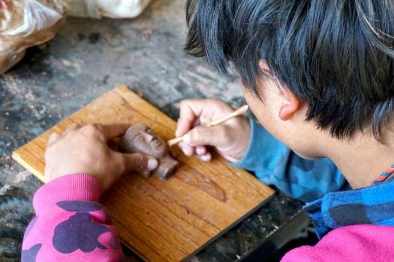 藏區當地年輕人正在泥塑傳習所裡製作泥塑(新華社)