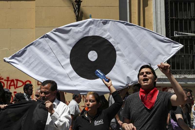 智利示威者高舉眼球圖案,抗議軍警在連月抗爭中暴力執法,造成逾200人失明。(AP)