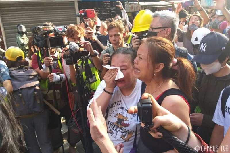 香港「反送中」抗爭學生的母親,在遭到警方嚴密包圍的理工大學外要求見子女一面。(翻攝香港大學學生會校園電視臉書)