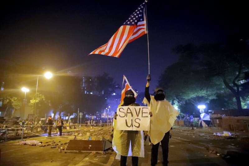 「反送中」抗爭者17日深夜在香港理工大學高舉美國國旗與「救救我們」(SAVE US)的標語。(美聯社)