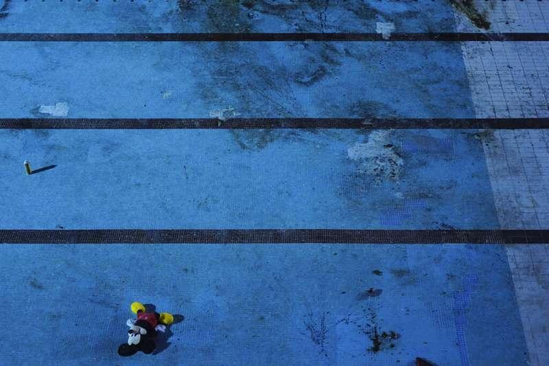 香港理工大學在圍城激戰後一片狼藉。圖為游泳池與被扔下的米奇玩偶。(AP)