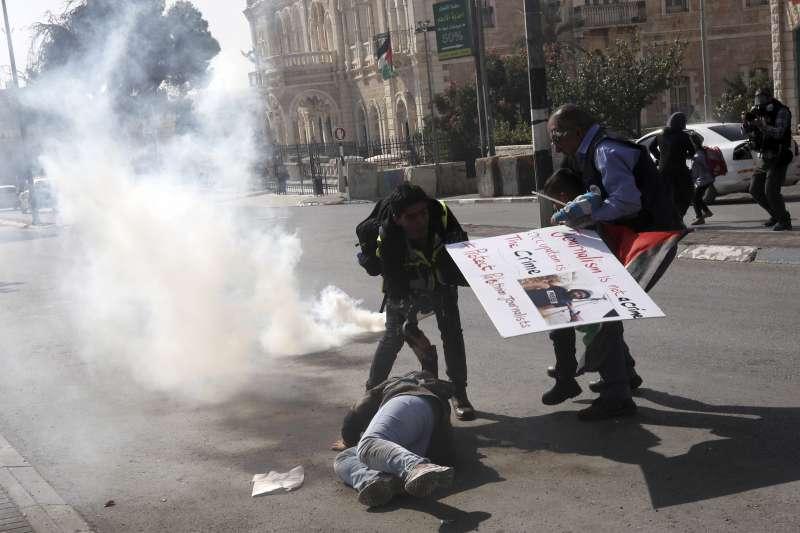 巴勒斯坦攝影記者阿瑪尼(Muath Amarneh)被以色列砲火擊中一眼失明,記者發動抗議同遭催淚彈攻擊。(AP)