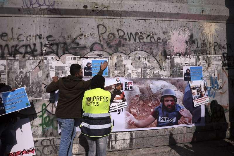 巴勒斯坦攝影記者阿瑪尼(Muath Amarneh)被以色列砲火擊中一眼失明,媒體同業發動抗議。海報上藍衣者為阿瑪尼。(AP)