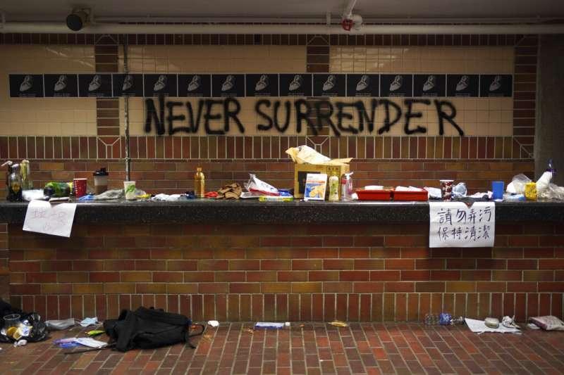 香港理工大學的內部情形,牆上用噴漆寫著「永不投降」。(美聯社)
