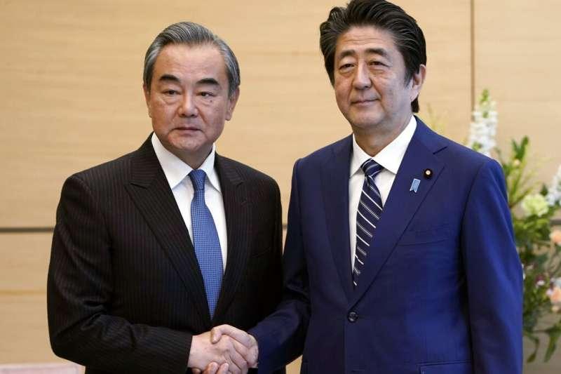 王毅(左)言明日本必須「妥善處理台灣問題」,安倍(右)至今未做任何表態。(美聯社)