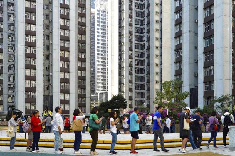 11月24日香港區議會選舉投票所外的人龍。(美聯社)