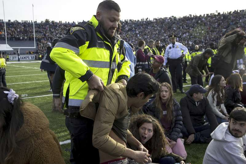 哈佛和耶魯的美式足球賽抗議者湧入示威,警方到場將抗議者帶走才恢復比賽。(美聯社)