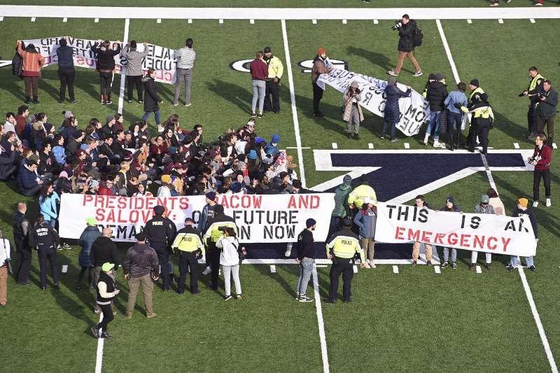 哈佛、耶魯的學生及校友衝入場內抗議學校投資石油業,成為氣候變遷的共謀。(美聯社)