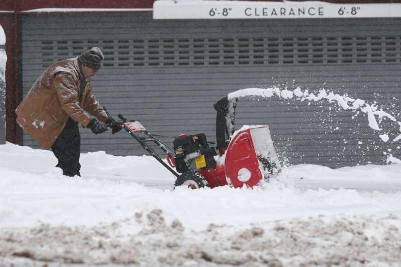 美國科羅拉多州丹佛,一名男子正用吹雪機清除人行道的積雪(美聯社)