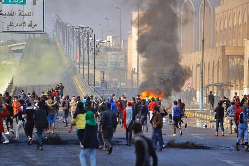 28日,伊拉克納希利亞市的示威者遭當局開槍鎮壓。(AP)