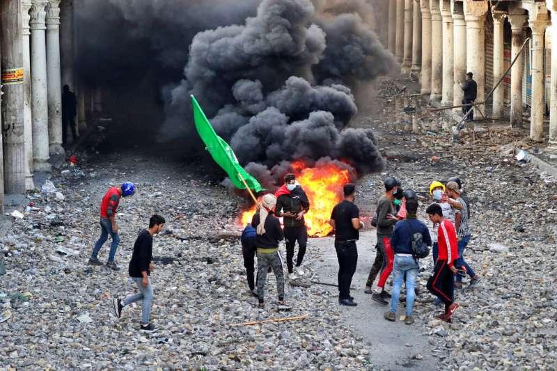 今年全球都不平靜,天災之外,示威抗議遍及各國。圖為伊拉克示威者遭當局開槍鎮壓。(AP)