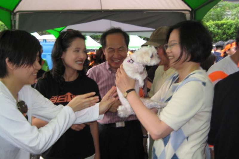 總統蔡英文(右一)擔任民進黨主席時被拍到抱起、撫摸小白狗,而小白狗主人正是楊蕙如(左一)。(中評社)