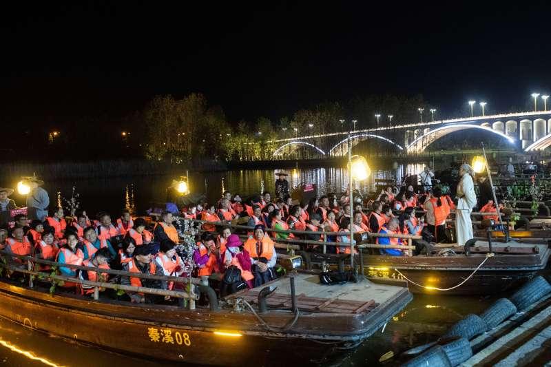 遊客們在湖南省常德市桃花源風景名勝區乘船觀看實景演出《桃花源記》。(新華社)