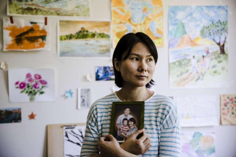 長期遭伊朗監禁的華裔學者王夕越,妻子曲樺捧著一家人的照片(AP)