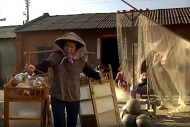 《金水嬸》電視劇照,擔著雜貨的金水嬸。(截取自文化部台灣文化工具箱網站)