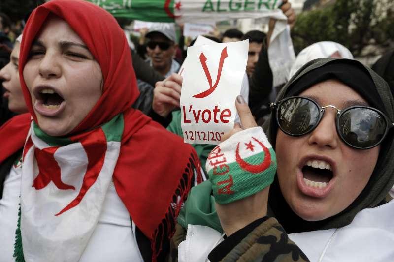 阿爾及利亞2019年總統大選,民眾抗議無法改變政治結構,標語寫著「拒絕投票」。(AP)