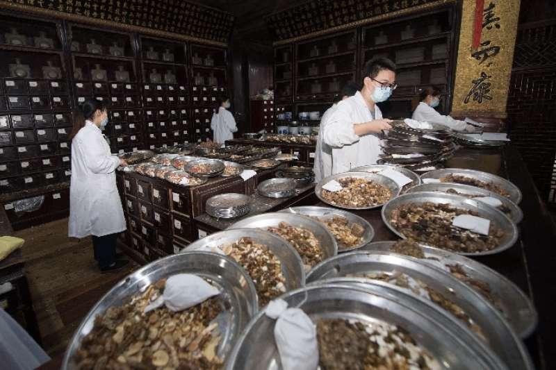胡慶餘堂工作人員在藥房以傳統手工的方式為顧客抓藥。(新華社)