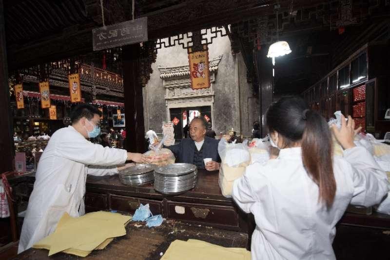 工作人員在胡慶餘堂藥房給顧客發放用牛皮紙包好的藥。(新華社)