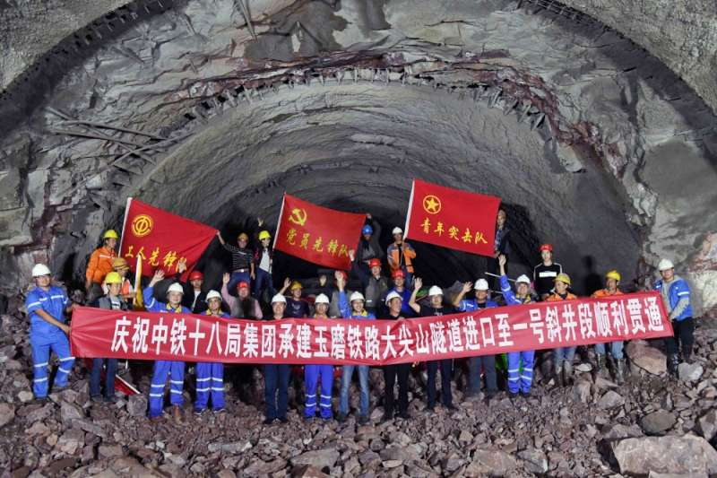 玉磨鐵路大尖山隧道進口至一號斜井段順利貫通。中鐵十八局集團的建設者在隧道現場慶祝貫通。(新華社)