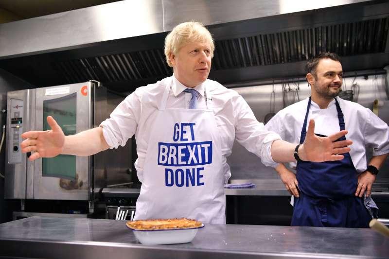 英國12日提前大選,首相強森把握最後機會亮相造勢,圍裙上寫著主打標語「搞定脫歐」。(AP)