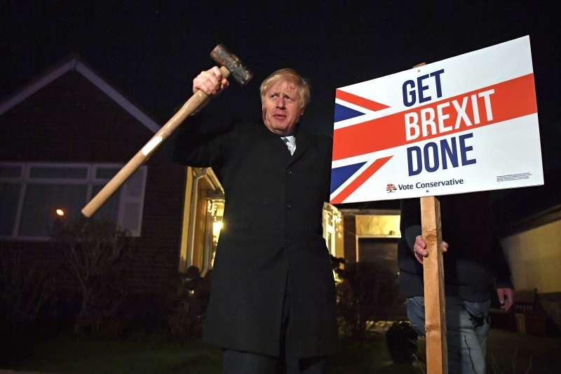 英國12日提前大選,首相強森把握最後機會亮相造勢,牌子寫著主打競選口號「搞定脫歐」。(AP)
