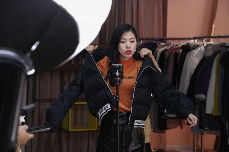 在11月27日的一場直播中,王溪梓在助理的幫助下穿上一件夾克,她同時還在繼續描述這件衣服的質地。 圖片來源:RAFFAELE HUANG/THE WALL STREET JOURNAL