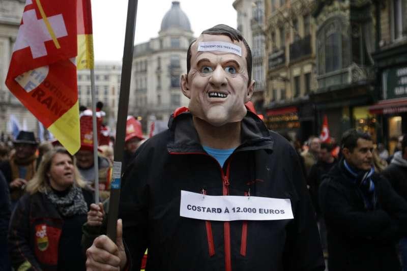 反對退休金改革的法國民眾帶著馬克宏的頭套上街示威。(美聯社)