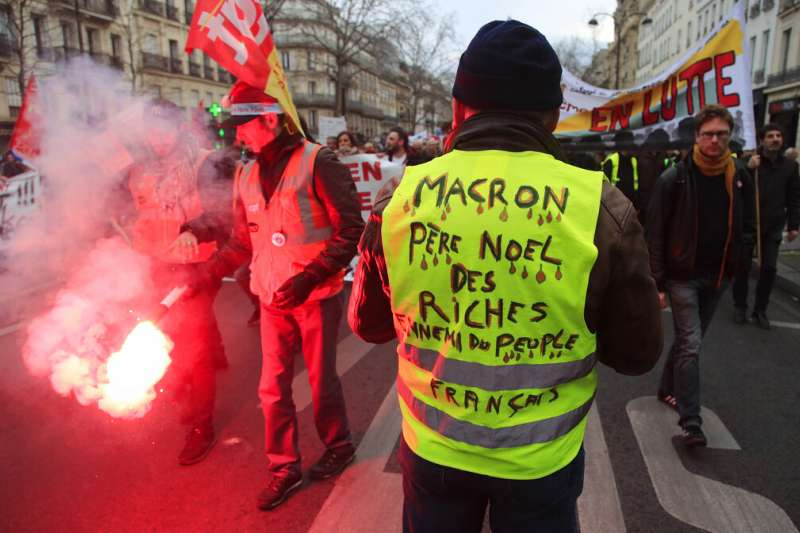 一名身穿黃背心的抗議者參加法國大罷工抗爭。(美聯社)