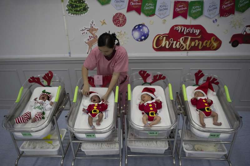 2019年12月24日,泰國一家醫院的護理師為新生兒換上耶誕裝扮。(AP)