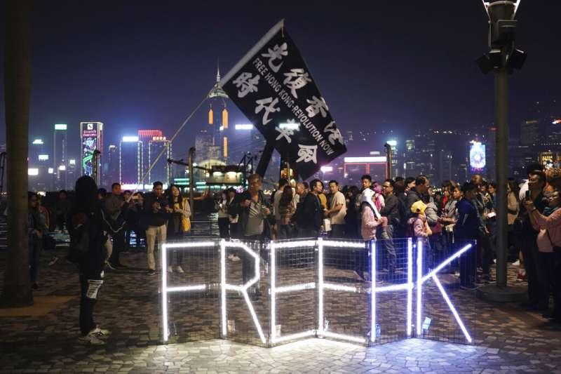 抗議政府的香港民眾在黑夜中高舉「光復香港,時代革命」的旗幟。(美聯社)