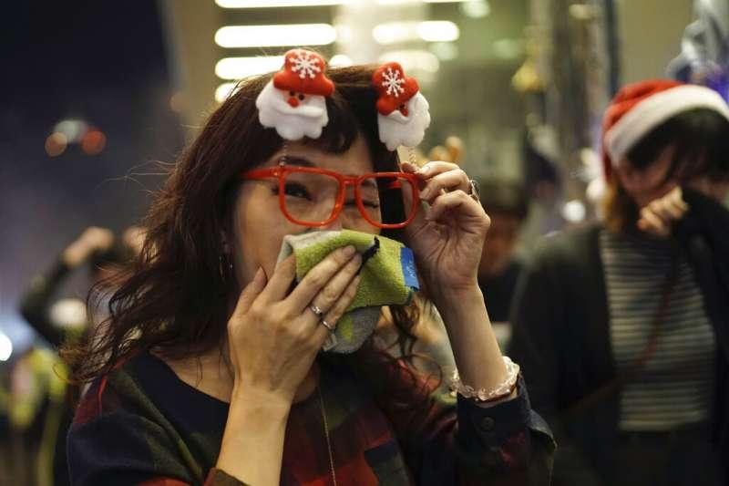香港警察在耶誕夜施放催淚彈,抗議民眾忙著摀住口鼻。(美聯社)
