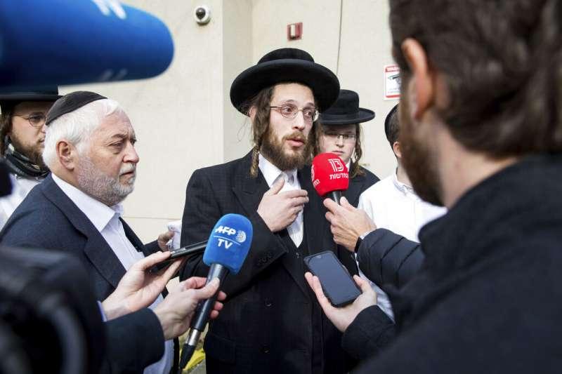 28日在拉比羅騰堡住處慶祝光明節的一名猶太人,正在對媒體講述他們如何阻止兇嫌殺人。(美聯社)
