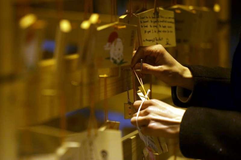 許多日本民眾趁新年到明治神宮參拜祈福,也把心願寫在繪馬上。(美聯社)
