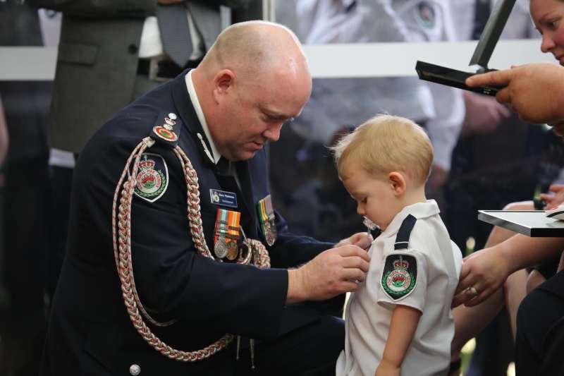 才19個月大的哈維含著奶嘴,代父親接受鄉村消防局所頒最高等級的英勇勳章。(取自新南威爾斯省RFS臉書)