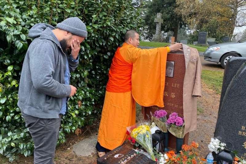 達摩難陀(釋福玉)法師在李小龍父子的墓地前祝禱追思。(圖/業者提供)