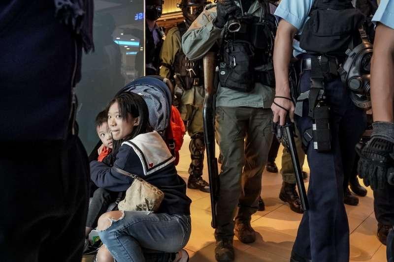 香港沙田區新城市廣場示威活動中,一名女子在警察經過時護著孩子。(ANTHONY KWAN FOR THE WALL STREET JOURNAL)