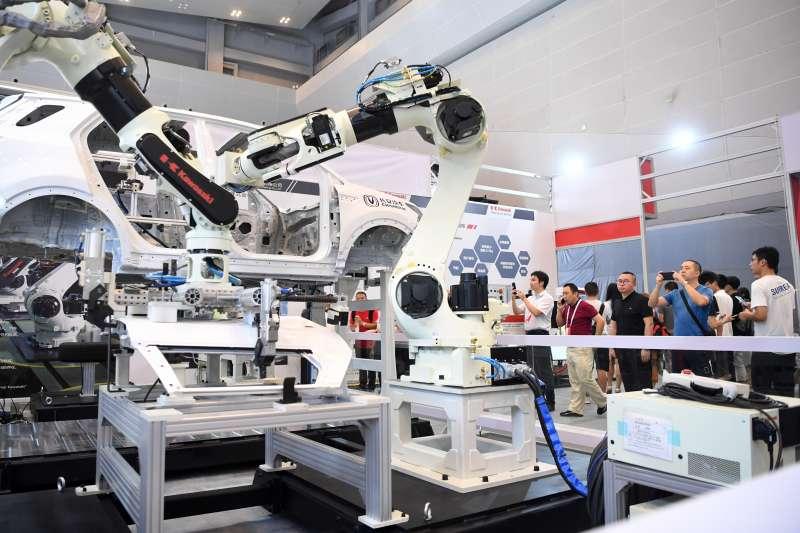 2019年中國國際智慧產業博覽會現場,組裝機器人吸引觀眾參觀拍照。(新華社)