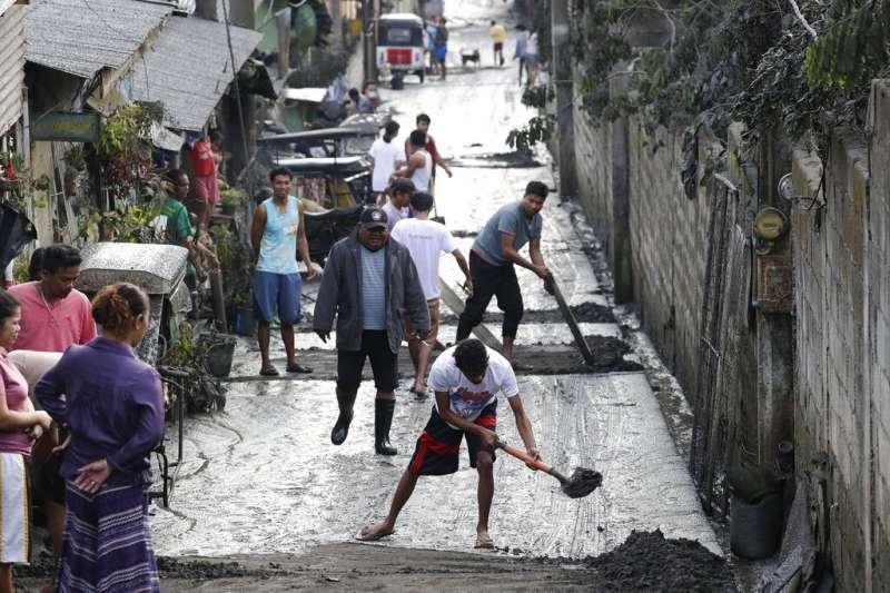 菲律賓塔爾火山12日噴發,附近民眾13日忙著清理火山灰。(美聯社)