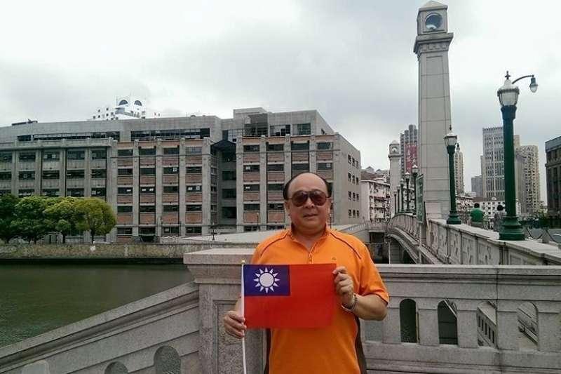 2015年吳斯懷在上海王行倉庫前秀國旗。(取自吳斯懷臉書)