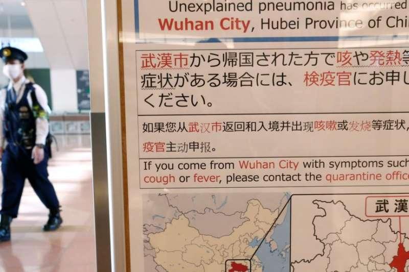 日本東京羽田機場一名戴著口罩的警察走過武漢肺炎的防疫廣告牌。(美國之音)