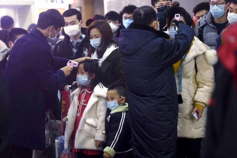 武漢肺炎疫情不斷升高,其他城市的火車站紛紛對武漢前來的旅客測量體溫。圖為杭州火車站。(美聯社)