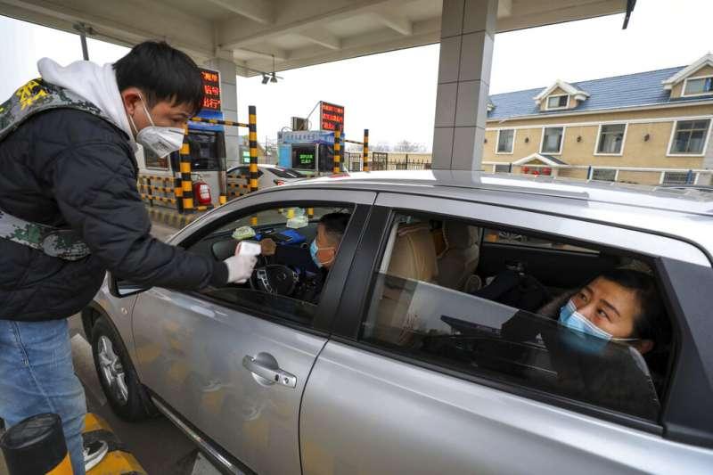 武漢肺炎疫情不斷升高,高速公路武漢收費站也對往來駕駛實施體溫檢測。(美聯社)