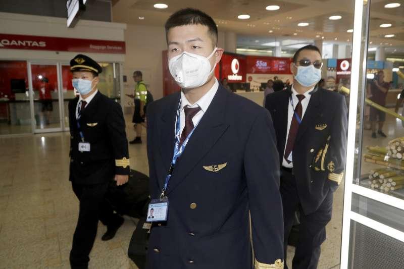 武漢肺炎全球擴散:從中國武漢飛抵澳洲雪梨的中國東方航空機組人員戴口罩(AP)