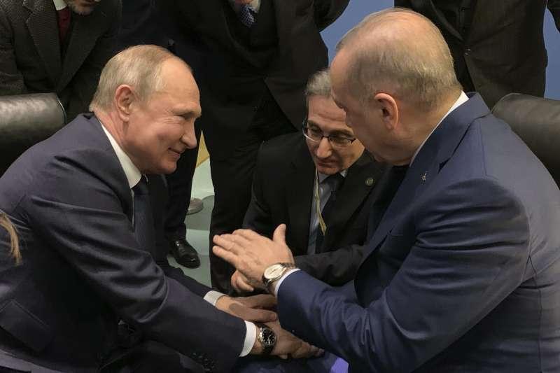 2020年1月19日,俄羅斯總統普京(左)與土耳其總統艾爾多安在商討利比亞問題的「柏林會議」上握手寒暄(AP)