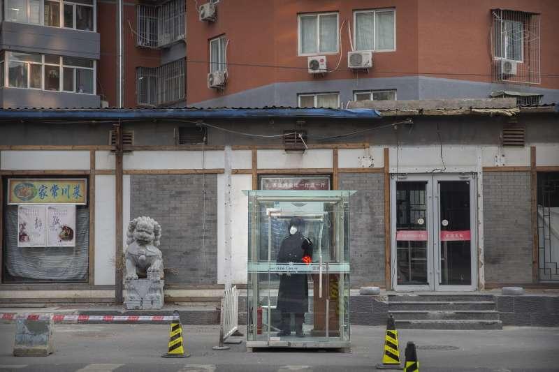 中國武漢肺炎疫情持續延燒,北京一名保安配戴口罩執勤(AP)