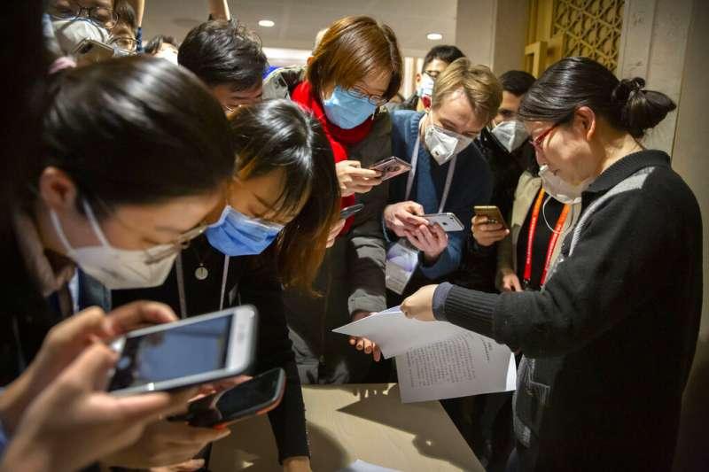 武漢肺炎疫情蔓延,各國媒體的記者在中國國務院召開的記者會上也都戴著口罩工作。(美聯社)