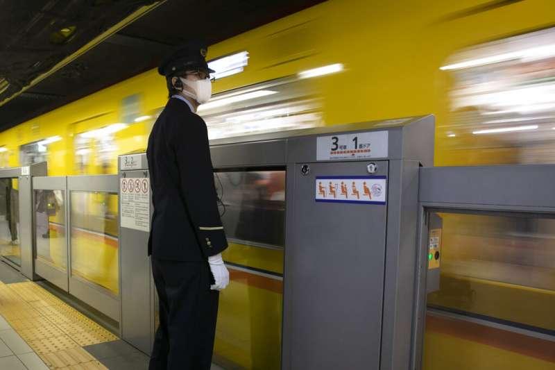 地鐵,電車,日本。武漢肺炎疫情蔓延,東京銀座的地鐵職員也戴上口罩工作。(美聯社)
