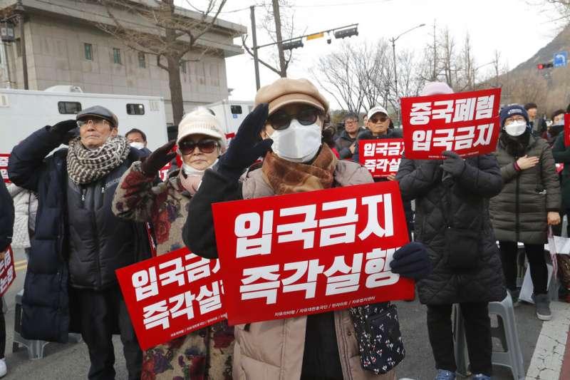 武漢肺炎疫情延燒,部分南韓民眾在青瓦台附近舉牌抗議,要求政府禁止中國遊客入境。(美聯社)
