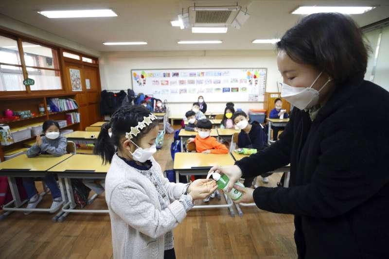 武漢肺炎疫情升高,南韓首爾的小學老師正為同學消毒。(美聯社)